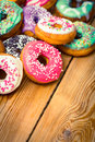 Colorful glazed donuts on the wooden table Royalty Free Stock Photos