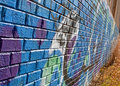Colorful graffiti covers a brick wall the of an abandoned warehouse Stock Image