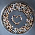 Colorful gravel stones in a corcle with heart in the middle Royalty Free Stock Photo