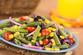 Colorful green bean salad fresh vegetarian made of beans cherry tomatoes sweet corn black olives and red onions on blue plate with Stock Image
