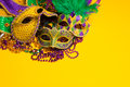 Colorful group of mardi gras or venetian masks a festive carnivale on a yellow background Royalty Free Stock Photo