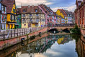 Colorful half timbered facades in medieval town colmar alsace reflecting water france Stock Photography
