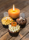 Colorful halloween cupcakes and candle top view a two tone burning on a rustic wooden table Stock Photography