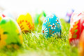 Colorful hand painted Easter eggs in grass. Spring theme, white copy-space