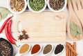 Colorful herbs and spices selection aromatic ingredients on wood table with cutting board for copyspace Stock Images