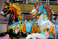 Colorful horses on carousel a pair of plastic mounted a children s roundabout Royalty Free Stock Image