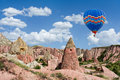 Colorful hot air balloon flying over Red valley at Cappadocia, Turkey Royalty Free Stock Photo