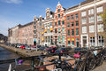 Colorful houses facades on the canal in amsterdam netherlands march embankment spring sunny day ordinary people are relaxing Royalty Free Stock Images