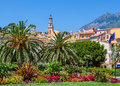 Colorful houses green trees and palms in menton catholic church s bell tower under blue sky as seen through france Royalty Free Stock Photography