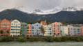 Colorful houses the river inn flows in front of a row of historic buildings in innsbruck austria peaks of the alps form the Royalty Free Stock Photo