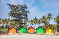 Colorful huts on the beach sandy at palm trees background in goa india Stock Photo
