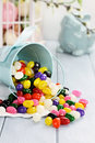 Colorful jelly beans a blue tin bucket tipped over spilling onto a table shallow depth of field Royalty Free Stock Images