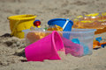 Colorful kids toys at the beach bright plastic are arranged in sand to create a fun day Royalty Free Stock Images