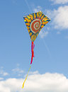 Colorful kite soaring against a blue sky Royalty Free Stock Image