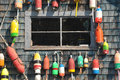 Colorful lobster floats hanging on a sea shack retired and buoys an old weathered clapboard side working dock Stock Image
