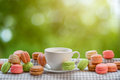 Colorful macaroons with cup of coffee on the napkin on blurred g