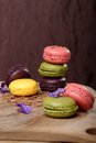 Colorful macaroons stacked on wooden plate Royalty Free Stock Photography