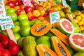 Colorful market fresh fruit display of including papaya grapefruit apples and pears in a Stock Photos