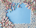 Colorful marshmallows candy frame on blue background Royalty Free Stock Photo