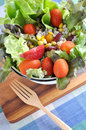 Colorful mixed salad bowl on wooden board with fork Stock Photography