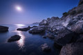 Colorful night landscape with full moon, lunar path and rocks in summer. Mountain landscape at the sea. Royalty Free Stock Photo
