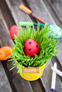Colorful painted easter egg on a fresh green grass in yellow bucket Stock Image