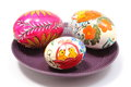 Colorful painted Easter egg on purple plate Royalty Free Stock Image