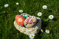 Colorful painted easter eggs on a basket on a green grass