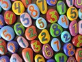 Colorful painted numbers on natural stones