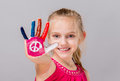 Colorful painted peace sign in a beautiful young girl.