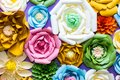 Colorful paper flowers on wall. Handmade artificial floral decoration. Spring abstract beautiful background and texture Royalty Free Stock Photo