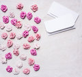 Colorful paper roses with envelopes, Valentine's Day border ,with text area  white wooden rustic background top view close up Royalty Free Stock Photo