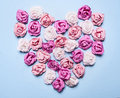 Colorful paper roses laid out in a heart shape on a blue background decorations Valentine's Day top view close up Royalty Free Stock Photo