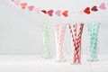 Colorful paper straws with a garland of hearts Royalty Free Stock Photo