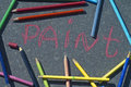 Colorful pencils and chalks overhead shot of the with hand drawn word paint in the center of image Royalty Free Stock Photo