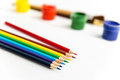Colorful pencils for drawing lying near gouache paints and brushes Royalty Free Stock Photo