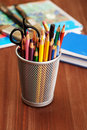 Colorful pencils in holder on wooden table and other stationery with objects background Royalty Free Stock Photography