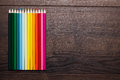 Colorful pencils over brown wooden table Royalty Free Stock Images
