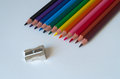 Colorful pencils with pencil sharpener on a sheet of white paperboard Royalty Free Stock Photo