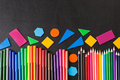 Colorful pencils in row and geometric figures on the black school chalkboard Royalty Free Stock Photo