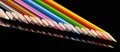 Colorful pencils in a row lots of on black reflective back Royalty Free Stock Photography
