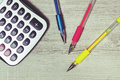 Colorful pens and calculator on the desk. Royalty Free Stock Photo