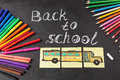 Colorful pens, pencils, title Back to school written by chalk and the school bus drawn on pieces of paper on chalkboar
