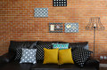 Colorful pillows on a sofa with brick wall in background Stock Photography