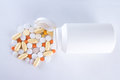 Colorful pills pouring from plastic bottle over white Stock Photography