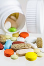 Colorful pills scattered from white bottle various on background Royalty Free Stock Images