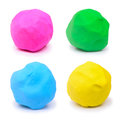 Colorful pink green blue and yellow plasticine clay on white background Stock Photos