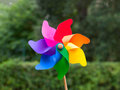 Colorful pinwheel in a garden trees blurred in background Royalty Free Stock Photo