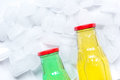 Colorful plastic bottles with ice cubes white desk background top view mockup Royalty Free Stock Photo