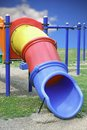 Colorful plastic slide blue yellow and red tube for children in the park Royalty Free Stock Image